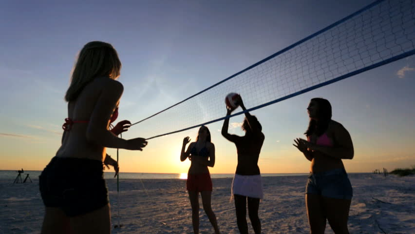 friends playing beach volleyball at sunset