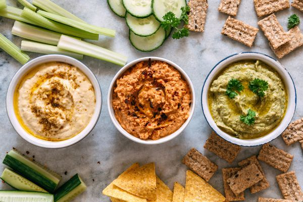 three dips surrounded by healthy snacks