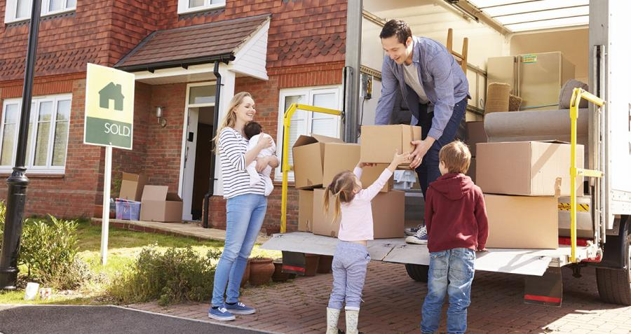 Young family with removal truck and boxes