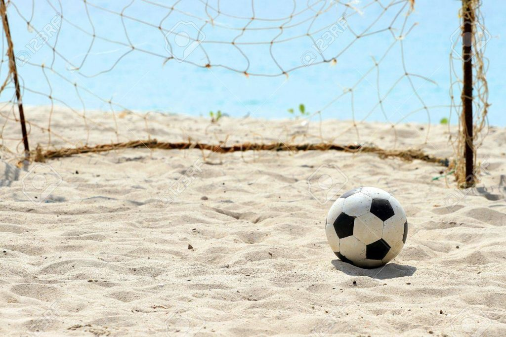 Soccar ball on sand infront of goals