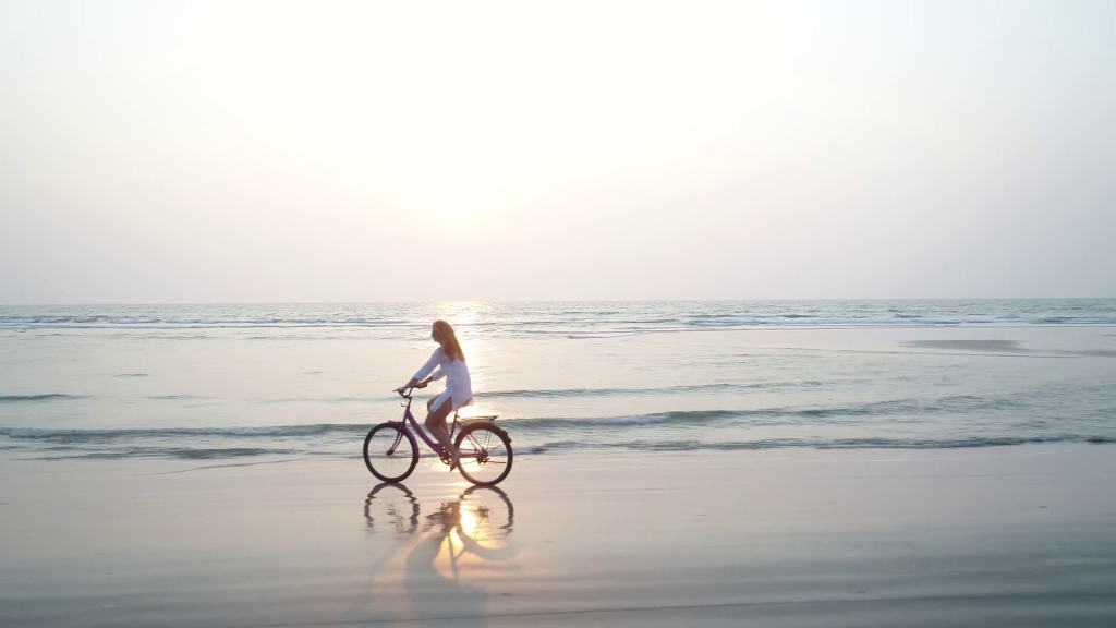 woman riding bicycle along the beach